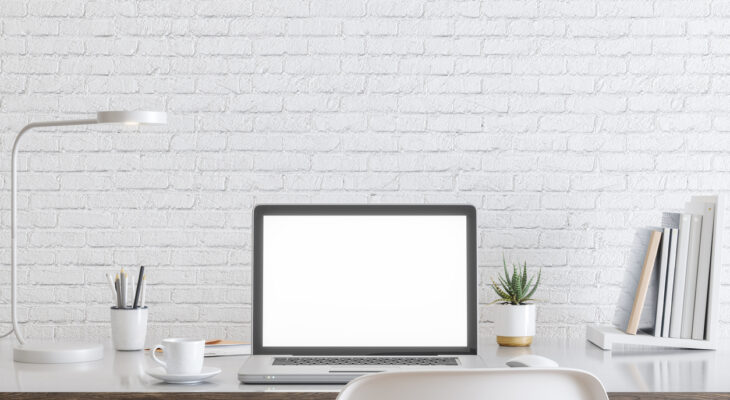Laptop with blank white screen, and office supplies on a desk